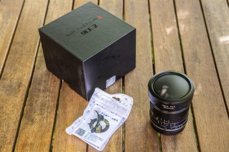 L'objectif 12mm f:2,8 de 7 Artisans, sa boîte et son accessoire pour bague de mise au point.